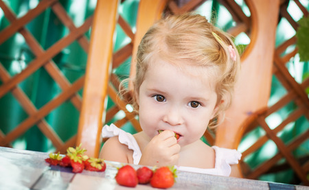 cute little girl eating strawberries photo