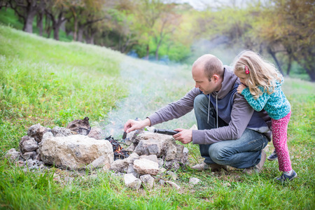 Camping: Dad shows little daughter how to make a fire Stock Photo