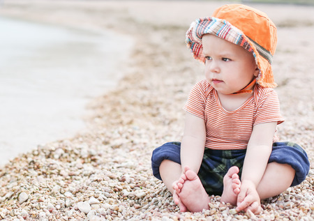 cute toddler baby  sitting on the beach looking at the sea photo