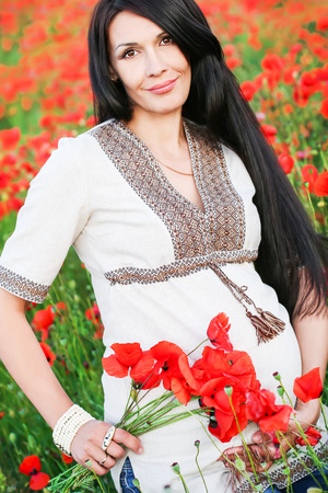 beautiful pregnant woman with a bouquet of poppies photo