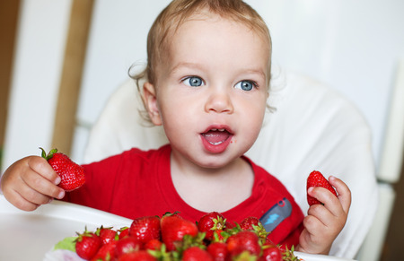 happy toddler boy eating strawberries on a white background