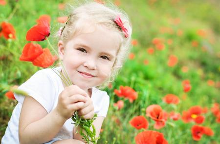 barrettes: carino bambina in possesso di un mazzo di papaveri