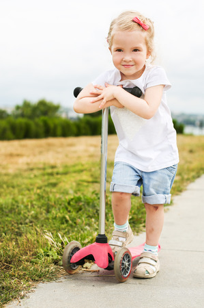 micro drive: cute little girl on scooter with bruises on the legs Stock Photo