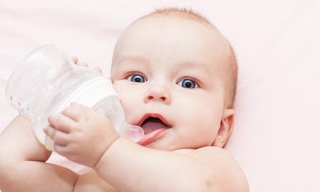 Happy baby is drinking water from a bottle Standard-Bild