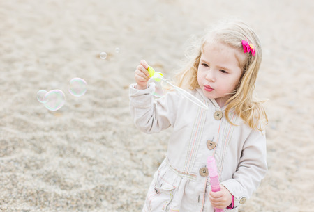 cute little girl blowing soap bubbles on the beach photo