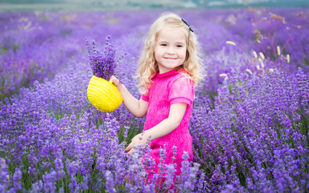 happy little girl is in a lavender field holds a basket of flowers photo