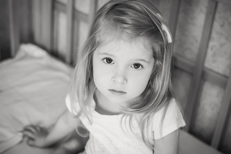 reluctance: portrait of a little girl sitting in bed ( black and white )