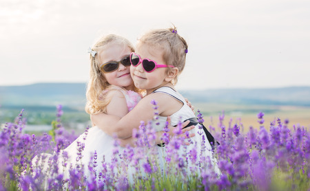 two little girls hugging on a lavender field photo