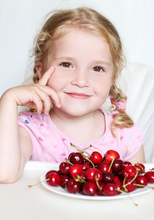cute little girl eating cherries on white background photo