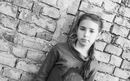 persona triste: triste niña de pie contra una pared de ladrillo (a blanco y negro)