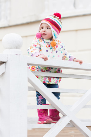 climbed: happy cute little girl for a walk, climbed on a white wooden fence