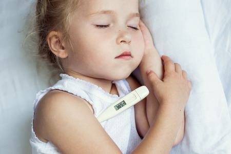 Sick little girl in bed with a thermometer