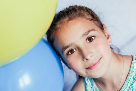 summer girl: portrait of a young girl with a yellow and blue ball