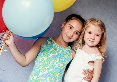 cute sisters with colorful balloons house photo