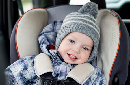 portrait happy toddler  boy sitting in the car seat  photo