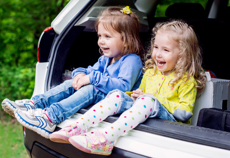 two happy kids in the car photo
