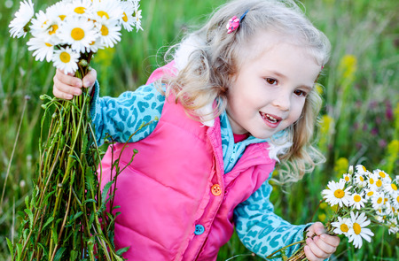 happy little girl holding a bouquet of daisies standing in a field