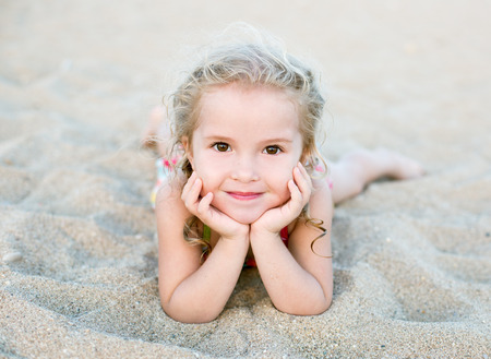 Happy little girl lying on the sand on the beach photo