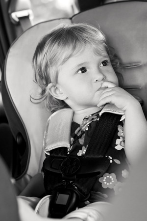 sucks: Cute baby sucks his finger sitting in the car seat  ( black and white ) Stock Photo