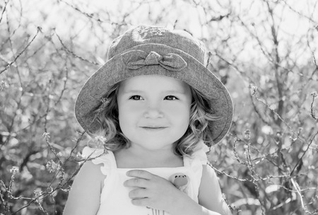 happy toddler girl in  in rape field with a toy in his hand ( black and white ) photo