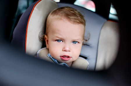 Portrait of a cute toddler boy sitting in the car seat