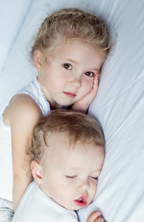 charming little brother and sister asleep on white background photo