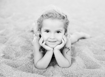 little girl beach: Happy little girl lying on the sand on the beach ( black and white )