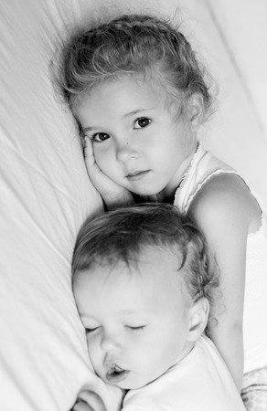 charming little brother and sister asleep on white background  ( black and white ) photo