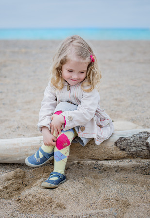 cute little girl sitting on the coast on a dry tree photo