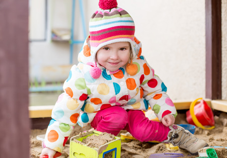 pit fall: cute little girl in a sandbox  in cold weather Stock Photo