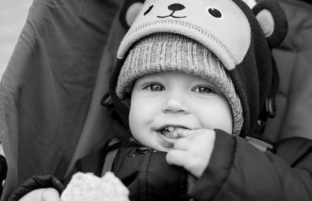 happy baby boy sitting in a stroller for a walk ( black and white ) photo
