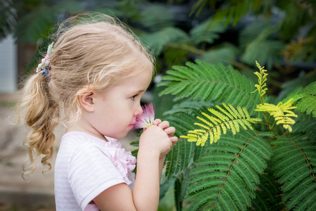 cute little girl smelling a pink flower photo