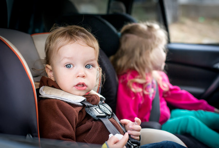 small children in car seats in the car photo