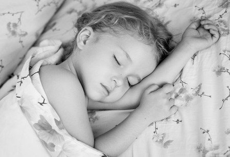 toddler girl is sleeping covered with a blanket  ( black and white )