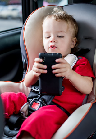 toddler boy playing smartphone in the car photo