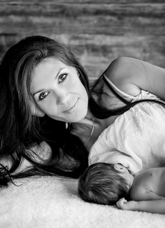 beautiful mother feeding her newborn with breast ( black and white ) photo