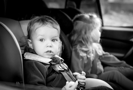 small children in car seats in the car ( black and white ) photo