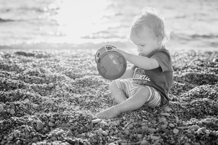 cute toddler boy playing on the beach at sunset ( black and white ) photo