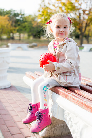 cute toddler girl sitting on the bench outdoor