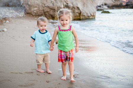 Small children brother and sister on the beach walk photo