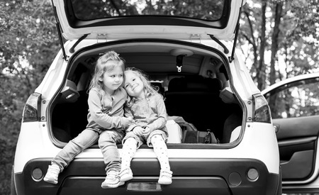 two cute little kids in the car ( black and white ) photo