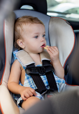 Happy Toddler boy in the car eating cookies