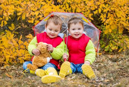 Happy toddler children under an umbrella in the autumn photo