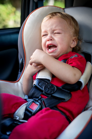 huilende baby jongen in autozetel Stockfoto