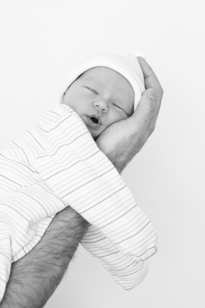 new born baby girl: newborn sleeps on a hand on a white background  (black and white)