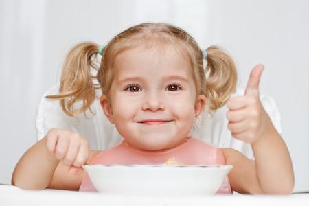 niños comiendo: feliz niña come con una cuchara mientras estaba sentado a la mesa en el fondo blanco