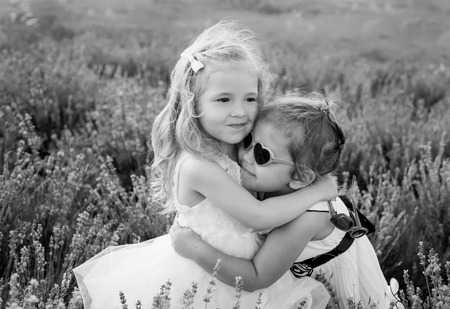 black and white: two little girls hugging on a lavender field ( black and white ) Stock Photo