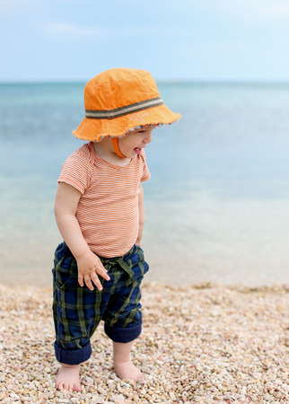Happy toddler boy walking on the beach barefoot photo