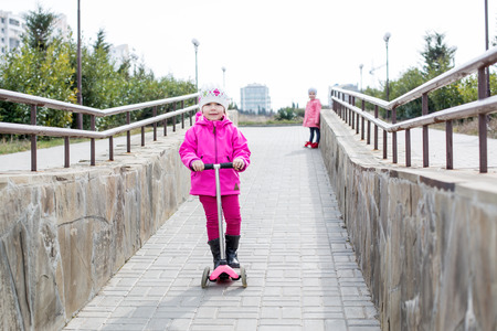 micro drive: Happy little girl on a scooter in a park with a friend Stock Photo