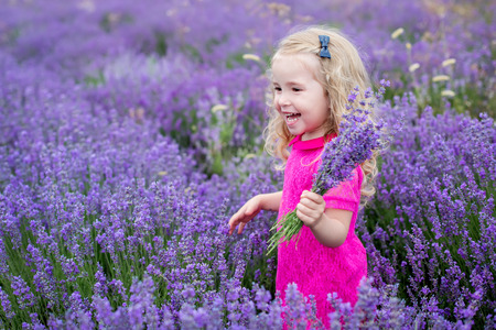 happy little girl in a field holding a bouquet of lavender
